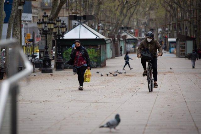 Una persona munta amb bicicleta i es protegeix amb una mascarilla durant el segon dia laborable de l'estat d'alarma pel coronavirus, a Barcelona (Espanya), a 17 de març de 2020.