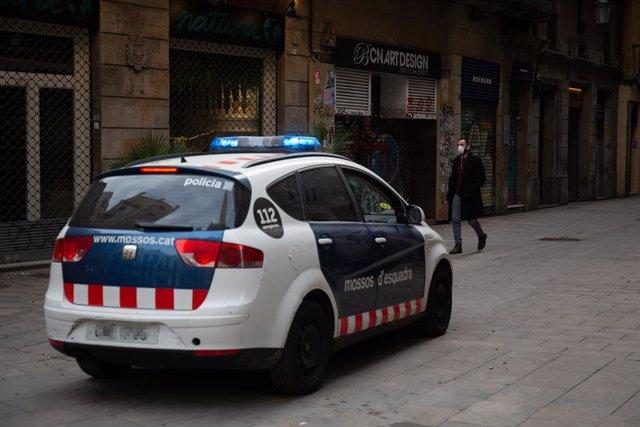 Un home amb mascarilla passeja per un carrer de Barcelona al costat d'un cotxe de la Policia en el segon dia laborable de l'estat d'alarma pel coronavirus, a Barcelona/Catalunya (Espanya), a 17 de març de 2020.