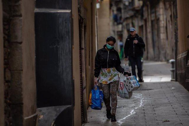 Una dona protegida amb mascarilla durant el segon dia laborable de l'estat d'alarma pel coronavirus, a Barcelona (Espanya), a 17 de març de 2020 (arxiu)