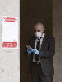 Un hombre con mascarilla y guantes manipula un móvil en las inmediaciones de un banco durante el primer día laborable desde que se decretó el estado de alarma en todo el territorio nacional a consecuencia del coronavirus, en Alcorcón (Madrid)