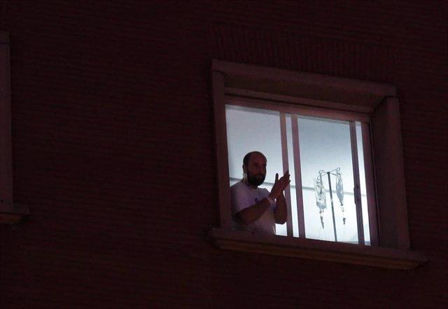 Un enfermo  sale a la ventana del hospital Virgen del Rocio de Sevilla, para aplaudir a los sanitarios. Sevilla a 18 de marzo 2019