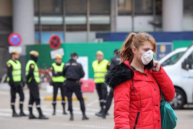 Una mujer con mascarilla circula cerca de donde se concentran efectivos de la Policía Nacional y del UME en las inmediaciones de la estación de tren Puerta de Atocha