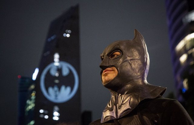 21 September 2019, Mexico, Mexico City: A man dressed as a Batman stands in front of a building that is illuminated with a Batman signet during a celebration of Batman's 80th birthday. Photo: Jair Cabrera Torres/dpa