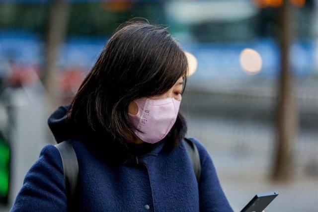 Una mujer asiática mira su móvil con una mascarilla protectora, mientras las farmacias registran una alta demanda de estas por parte de ciudadanos chinos tras el coronavirus, en Madrid (España), a 30 de enero.