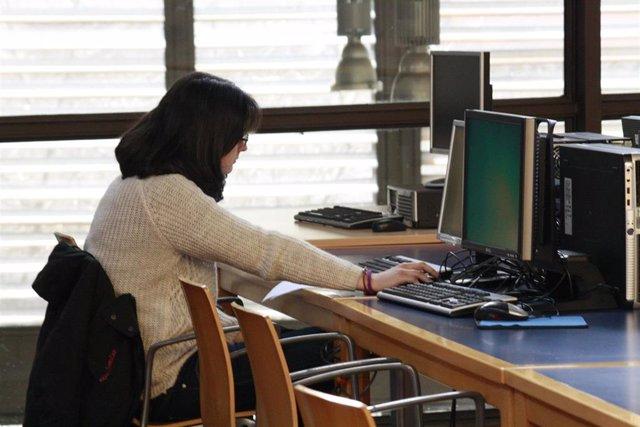Una estudiante consultando un ordenador.