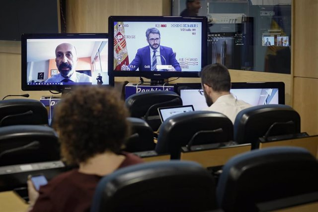 El ministro de Salud, Joan Martínez Benazet, desde su casa, y el ministro Portavoz, Eric Jover, en dos pantalas situadas en la sala de prensa del Gobierno.