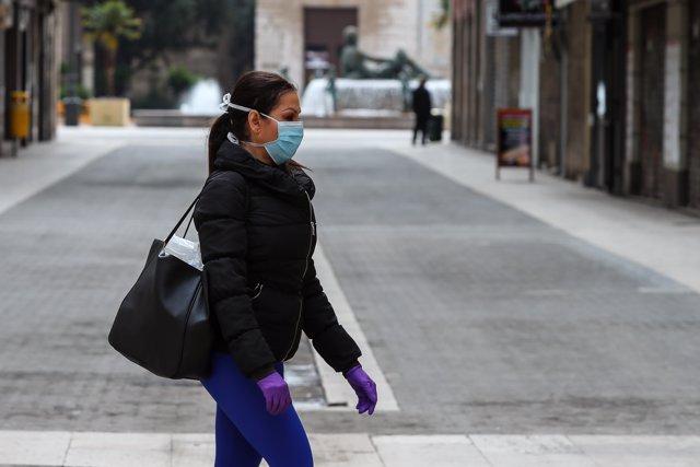 Una mujer camina con mascarilla y guantes de látex durante el cuarto día del estado de alarma por coronavirus, en Valencia/Comunidad Valenciana (España) a 19 de marzo de 2020.
