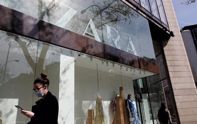 Una mujer con mascarilla pasa junto al escaparate de la tienda Zara de la Calle Princesa de Madrid del grupo Inditex