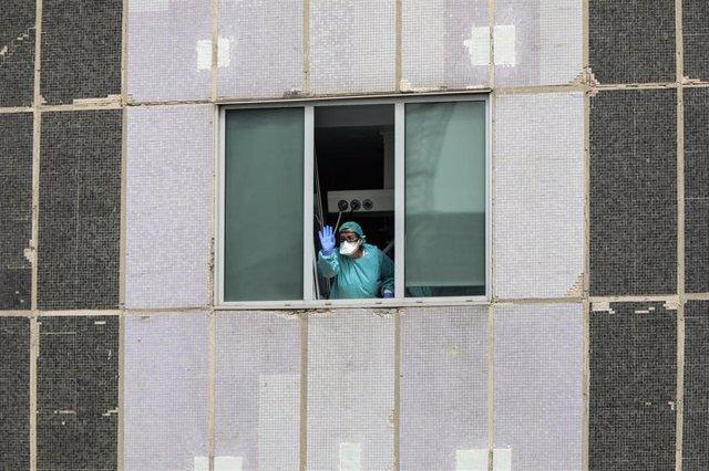 Una sanitaria del Hospital de La Paz totalmente protegida saluda y agradece el apoyo desde una de las ventanas del centro donde se lucha contra el coronavirus, en Madrid (España), a 18 de marzo de 2020.