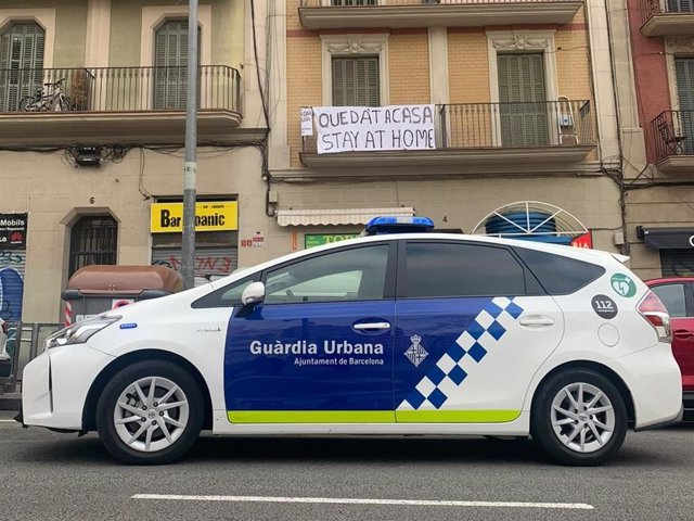 Un coche de la Guardia Urbana de Barcelona ante una pancarta con el lema 'Quédate en casa' por la pandemia de coronavirus.