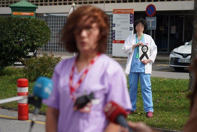 Una sanitaria del Osakidetza (servicio vasco de salud)  del Hospital de Galdakao responde a los medios mientras otra profesional sostiene un lazo negro de luto en recuerdo a la enfermera de 52 años fallecida por Covid-19