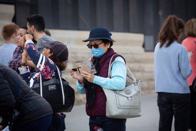 Una mujer utiliza su móvil en zonas cercanas a la Sagrada Familia protegida con mascarilla ante el avance del coronavirus en Barcelona
