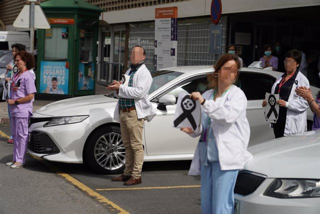 Trabajadores de Osakidetza (servicio vasco de salud)  del Hospital de Galdakao sostienen un lazo negro de luto mientras otros aplauden en recuerdo a la enfermera de 52 años fallecida por Covid-19 donde desarrollaba su labor profesional en la sexta planta.