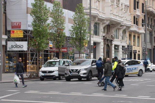 Transeúntes cruzan un paso de cebra de la Gran Vía madrileña que amanece totalmente vacía durante el sexto día de confinamiento por coronavirus en el país, en Madrid, (España), a 20 de marzo de 2020.