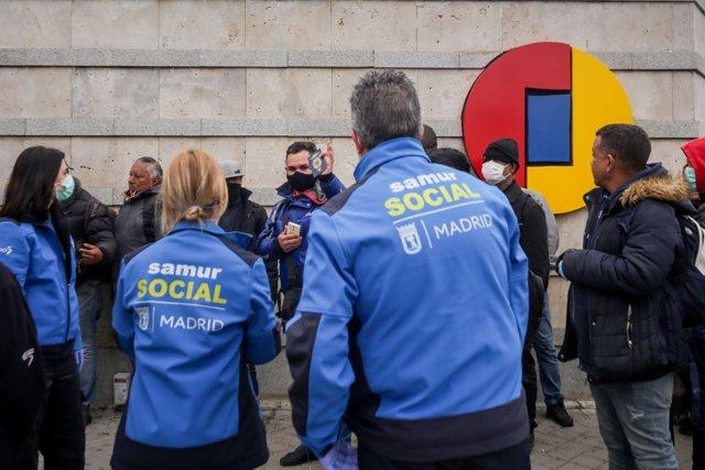 Trabajadores del Samur Social junto a algunas de las personas sin hogar que ocuparán el pabellón 14 de Feria de Madrid, que ha sido acondicionado para sintechos mientras dure la crisis del coronavirus, en Madrid (España), a 20 de marzo de 2020.