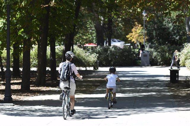 Una mare i el seu fill passegen amb bicicleta en un parc de Madrid.