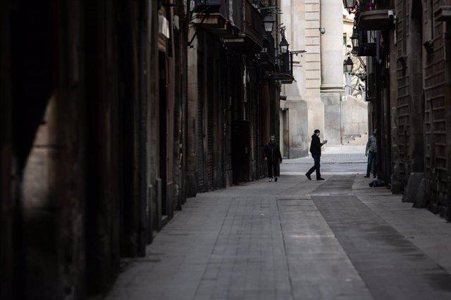 Una persona camina per un carrer de Barcelona durant el tercer dia laborable de l'estat d'alarma per coronavirus, a Barcelona/Catalunya (Espanya) a 18 de març de 2020.
