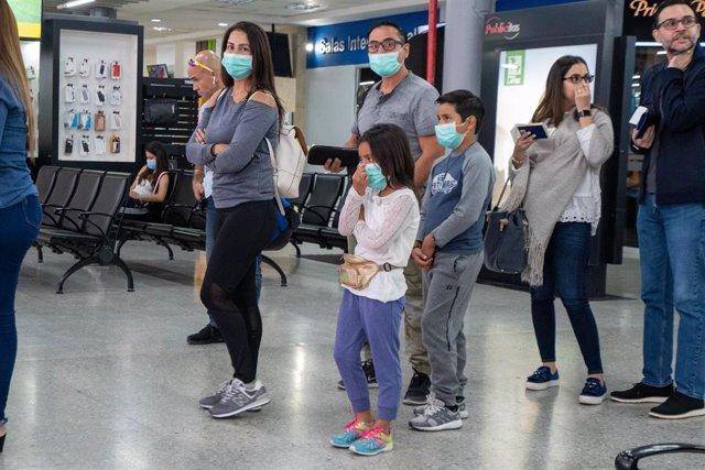 Imagen de pasajeros con mascarillas en un aeropuerto de Honduras.