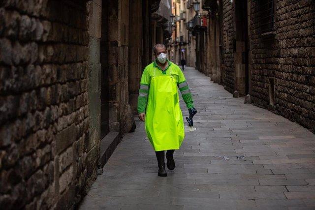 Un trabajador con mascarilla anda por una calle de Barcelona durante el tercer día laborable del estado de alarma por coronavirus, en Barcelona/Catalunya (España) a 18 de marzo de 2020.