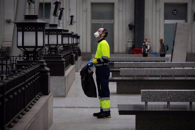 Un treballador de la neteja treballa protegit amb una mascarilla durant el segon dia laborable de l'estat d'alarma pel coronavirus, a Barcelona (Espanya), a 17 de març de 2020.