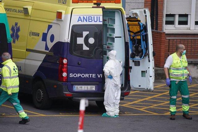 Varios sanitarios protegidos, uno con un traje y otro con mascarilla y guantes de látex, junto a una ambulancia en el Hospital Universitario Cruces, uno de los hospitales públicos vascos de referencia para infectados por coronavirus, en Bilbao/Euskadi (Es