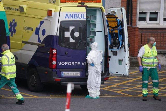 Diversos sanitaris protegits, un amb un vestit i un altre amb mascarilla i guants de ltex, al costat d'una ambulncia a l'Hospital Universitari Creus, un dels hospitals públics bascos de referncia per infectats per coronavirus, a Bilbao/Euskadi (És