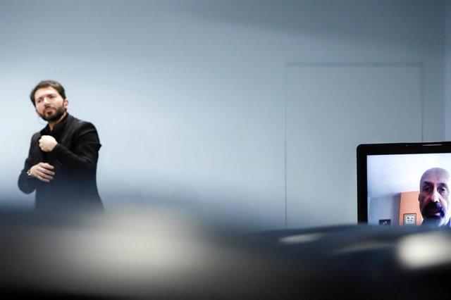 L'intrpret del llenguatge dels signes i el ministre de Salut, Joan Martínez Benazet, en la pantalla, a la sala de premsa del Govern durant la compareixena del divendres