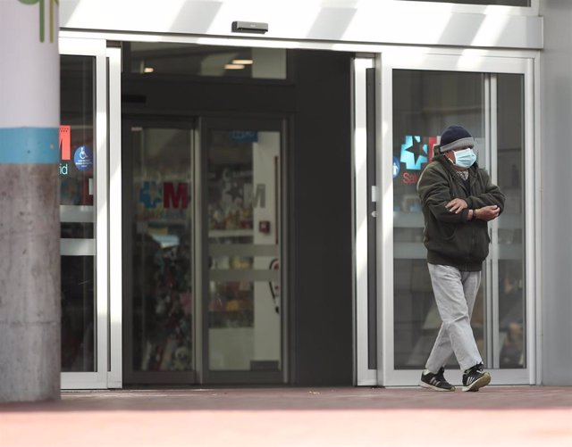 Un hombre con mascarilla camina por las zonas exteriores del Hospital de Torrejón.