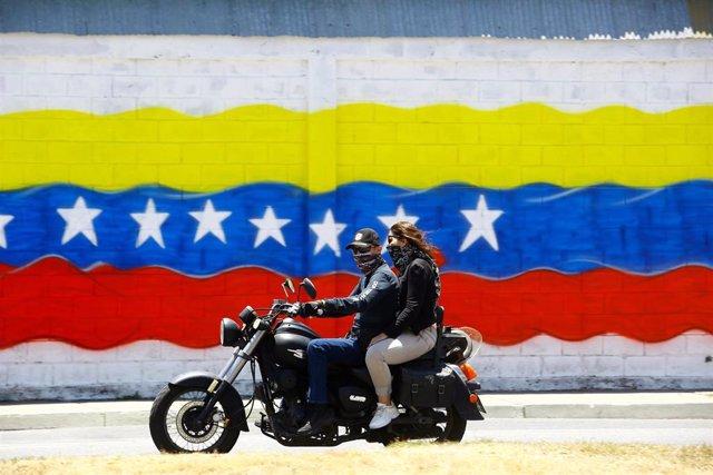 Jóvenes con mascarilla frente a una bandera de Venezuela