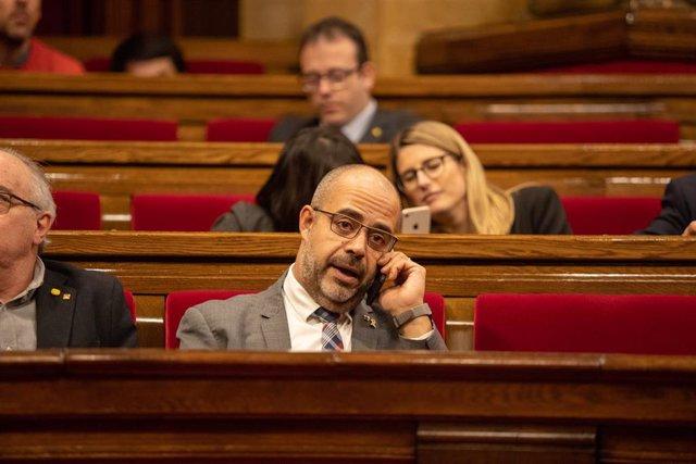 El conseller de Interior de la Generalitat, Miquel Buch, hablar por el móvil en su escaño durante un pleno extraordinario convocado tras la decisión de la Junta Electoral Central (JEC) de inhabilitar al president de la Generalitat, en Barcelona (Cataluña,