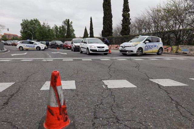 Un agente de la Policía Municipal habla con un conductor para comprobar si su viaje está justificado, en un control policial en la Glorieta del Marqués de Vadillo durante el sexto día de confinamiento por coronavirus en el país, en Madrid (España) a 20