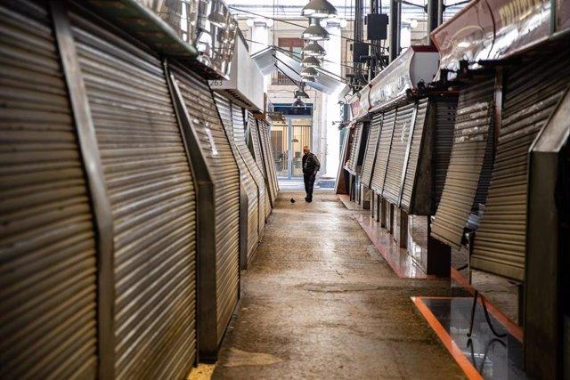 Un hombre pasea entre los puestos del Mercado de la Boquería, parcialmente cerrado durante el sexto día de confinamiento tras la declaración del estado de alarma por la pandemia de coronavirus, en Barcelona / Cataluña (España), a 20 de marzo de 2020.