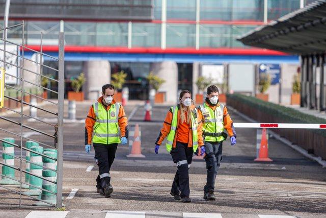 Tres miembros del personal de Emergencias Madrid con mascarillas a la entrada del Palacio de Congresos Municipal de Madrid, Ifema, donde se ha construido un 'hospital de campaña', en Madrid (España) a 22 de marzo de 2020.