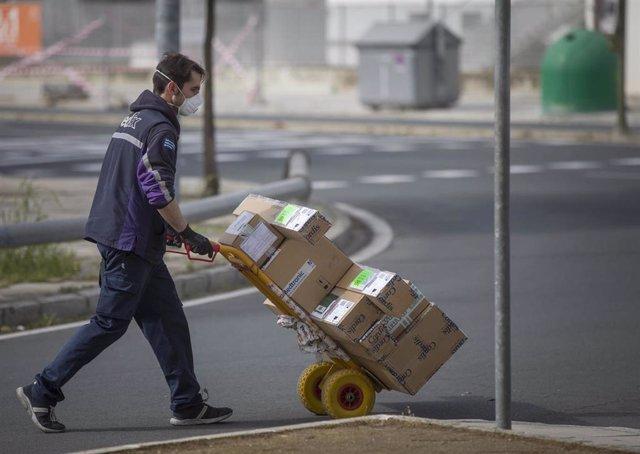Un trabajador de una empresa de reparto durante el sexto día de confinamiento por coronavirus en su jornada laboral ya que es uno de los pocos colectivos que tiene permitido seguir con su actividad. Sevilla (Andalucía,España), a 20 de marzo de 2020.