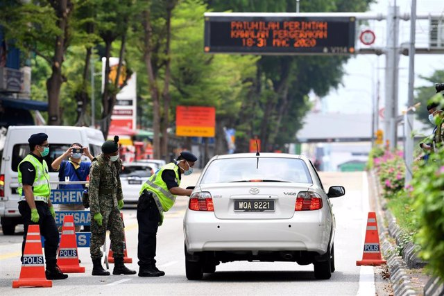 22 March 2020, Malaysia, Kuala Lumpur: Secuity officers stops a car at a checkpoint amid strict movement restrictions as part of the measures aiming to slow the spread of Coronavirus. Photo: Hazim Mohammad/BERNAMA/dpa