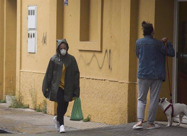 Dos personas transitan por el barrio de San Jerónimo durante el sexto día de confinamiento por coronavirus, en Sevilla