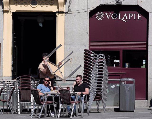 Dos hombres en una terraza de Madrid mientras un empleado recoge una de las mesas un día antes de que se cierre toda la hostelería para frenar contagios por coronavirus, en Madrid (España) a 13 de marzo de 2020.