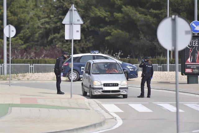 Dos policias nacionales paran a un coche estacionado durante el estado de alarma en el país por el coronavirus, en Huesca, Aragón (España)