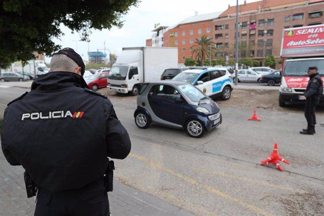 Dos policías detienen a los vehículos en uno de los controles por el estado de alarma del Covid-19