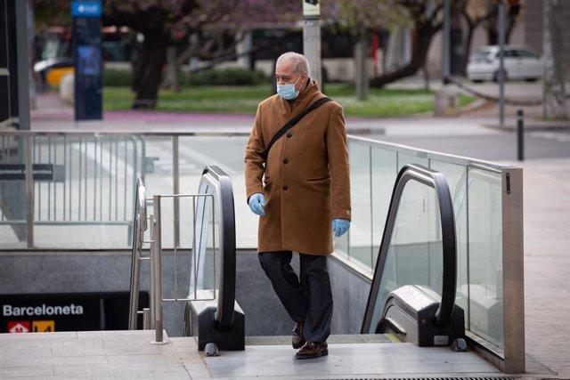 Un hombre protegido con una mascarilla y guantes de látex sale del metro durante el segundo día laborable del estado de alarma por el coronavirus, en Barcelona/Catalunya (España), a 17 de marzo de 2020.