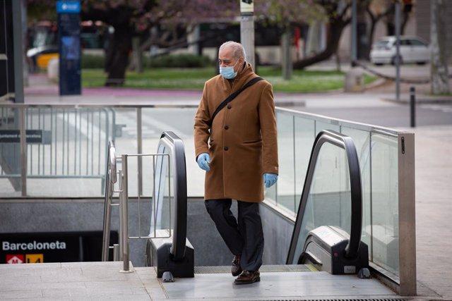 Un home protegit amb una mascarilla i guants de làtex surt del metre durant el segon dia laborable de l'estat d'alarma pel coronavirus, a Barcelona/Catalunya (Espanya), a 17 de març de 2020.