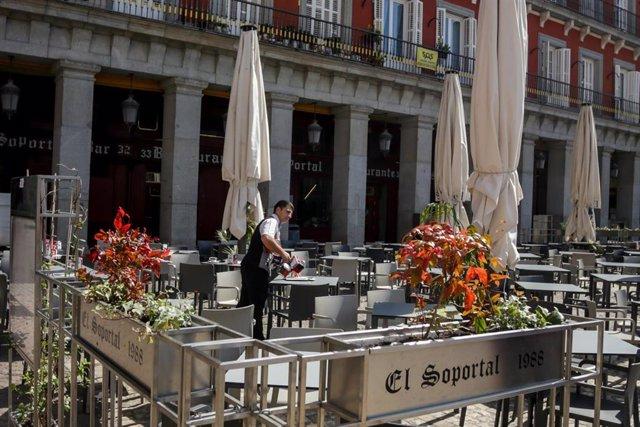 Un empleado de un bar en la Plaza Mayor de Madrid comienza a recoger la terraza un día antes de que se cierre toda la hostelería para frenar contagios por coronavirus, en Madrid