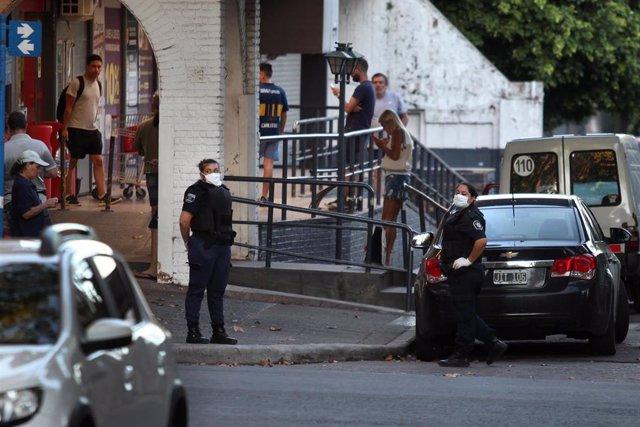 Trabajadora de seguridad con mascarilla frente a un supermercado en Buenos Aires, Argentina