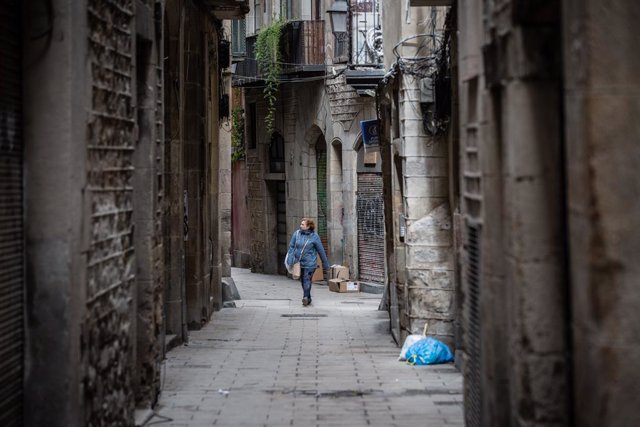 Una dona camina per un carrer de Barcelona durant el segon dia laborable de l'estat d'alarma pel coronavirus, a Barcelona (Espanya), a 17 de març de 2020.