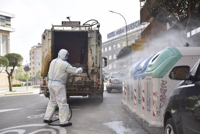 Un trabajador protegido de cuerpo entero desinfecta los cubos de basura y de reciclaje en el cuarto día laborable del estado de alarma por coronavirus, en Huesca, Aragón (España), a 19 de marzo de 2020.