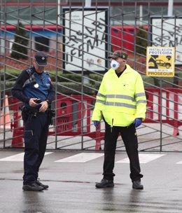 Un empleado de seguridad (d) y un Policía Municipal de Madrid (i) vigilan una de las entradas a IFEMA durante el tercer día de funcionamiento y primera fase del hospital provisional.