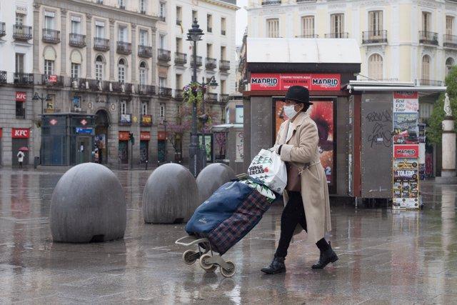 Una mujer protegida con mascarilla camina tras hacer la compra por la céntrica Puerta del Sol, prácticamente vacía durante el inicio de la segunda semana del estado de alarma por coronavirus, en Madrid (España) a 23 de marzo de 2020.