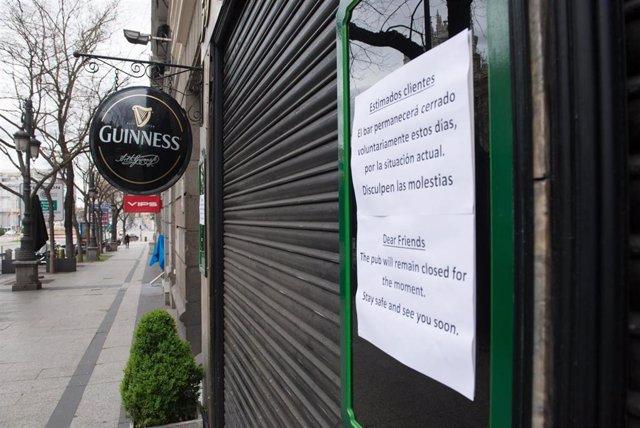 Entrada de un bar con un cartel en la entrada en la que se avisa de su cierre temporal, durante el estado de alarma decretado por el coronavirus, en Madrid (España), a 16 de marzo de 2020.