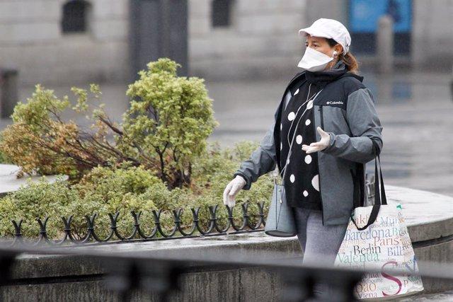 Una mujer protegida con mascarilla y guantes sanitarios realiza compras durante el sexto d'a del estado de alarma por coronavirus.