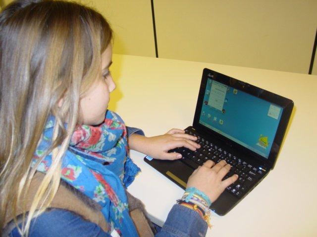 Una escolar, con un ordenador portátil.